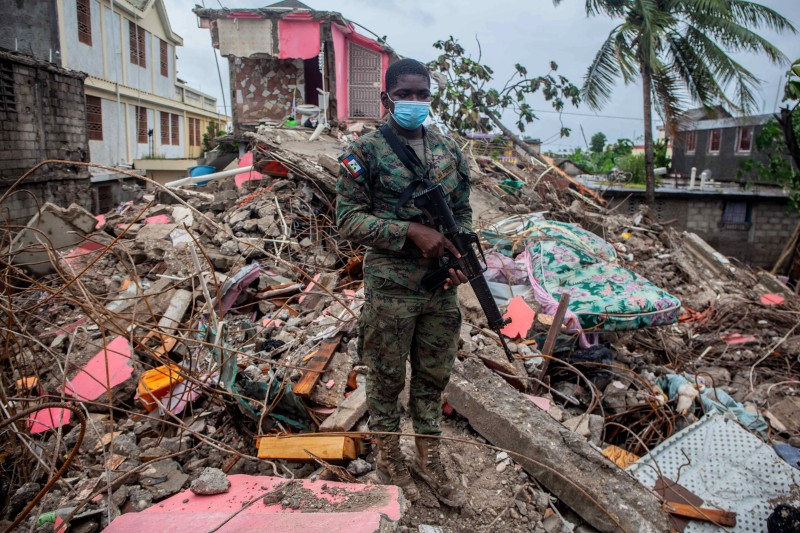 A soldier stands over debris in Haiti.