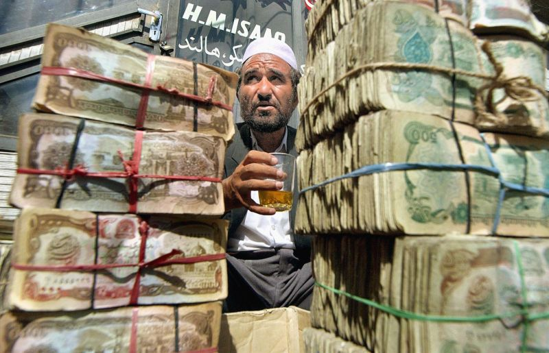 Abdul Aziz, an elder Afghan money changer, takes a break sitting behind bundles of afghanis at the main currency exchange market in Kabul on July 18, 2002.