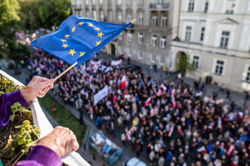 An elderly woman waves a European Union flag in Poland.