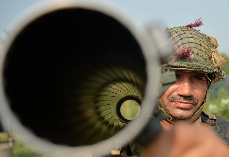 An Indian Border Security Force (BSF) soldier carries a rocket launcher as he takes up position with colleagues at an outpost along a fence at the India-Pakistan border in R.S Pora southwest of Jammu on Oct. 2, 2016.