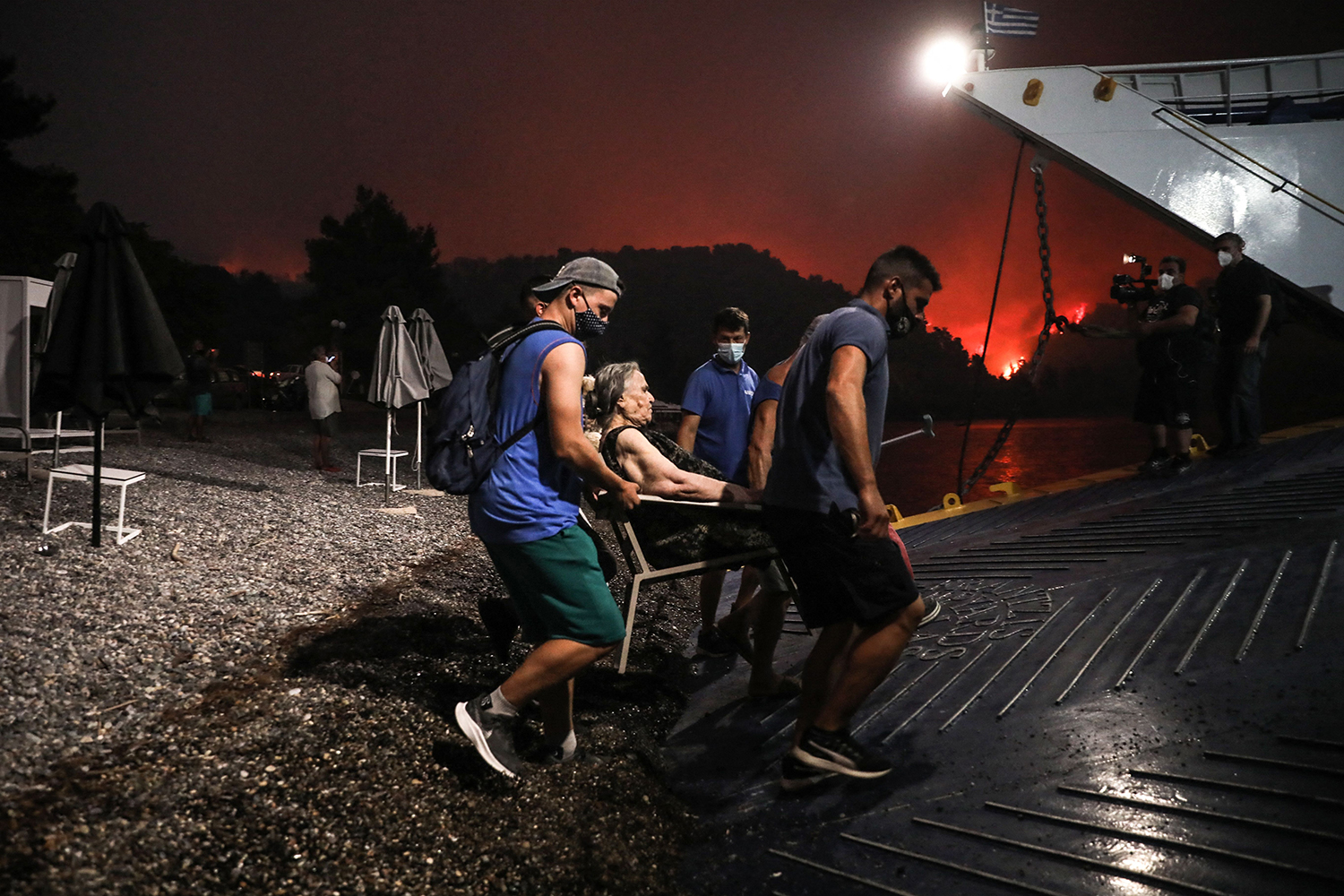 People board a ferry as a wildfire approaches in Greece.