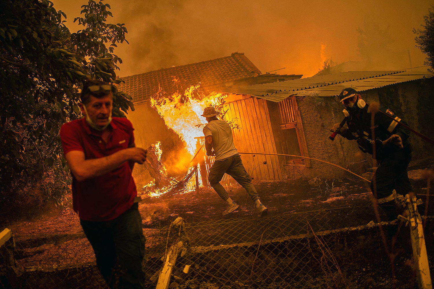 A firefighter and locals rush to a burning house in Greece.
