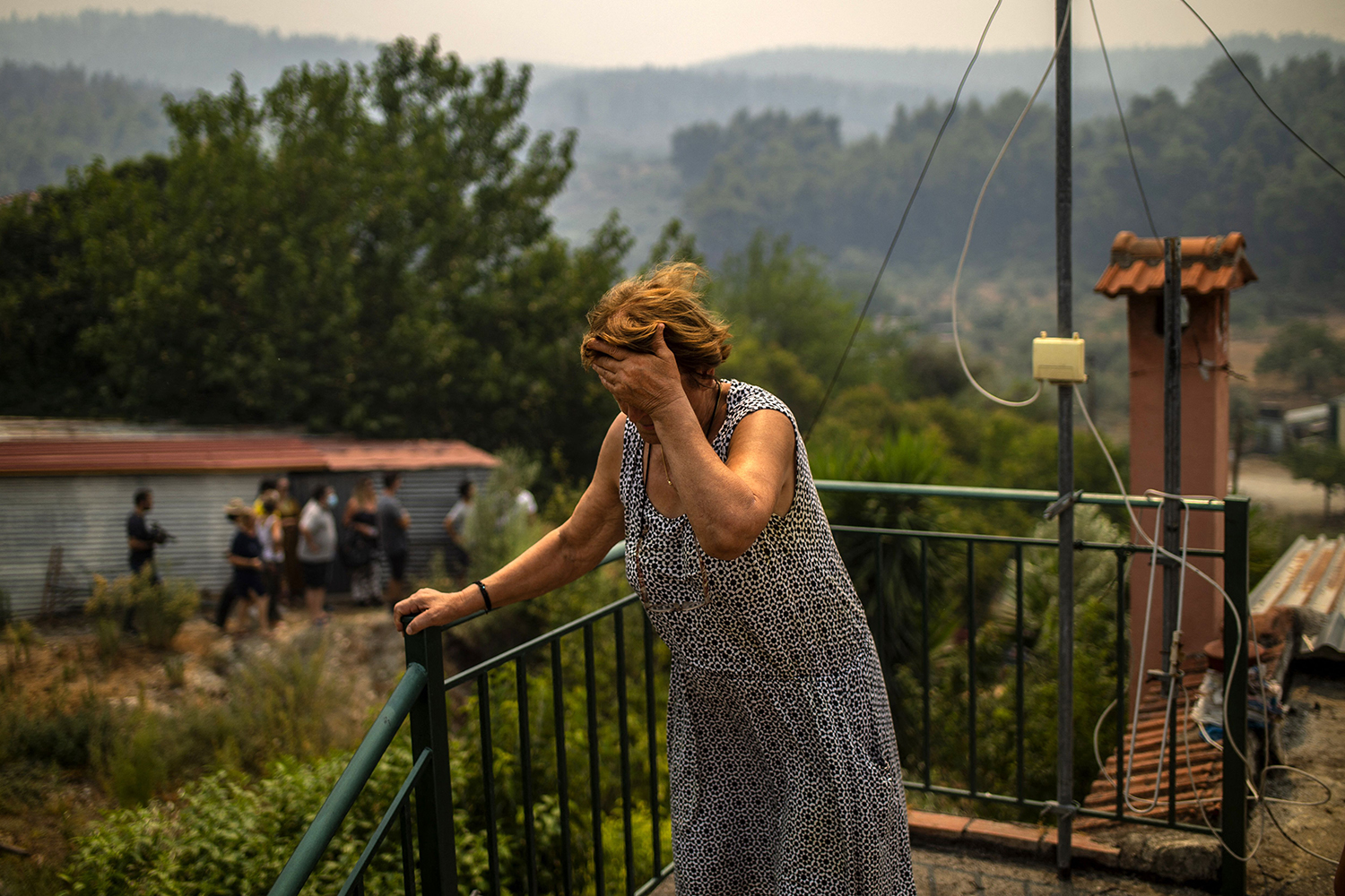 Woman reacts to fire in Greece