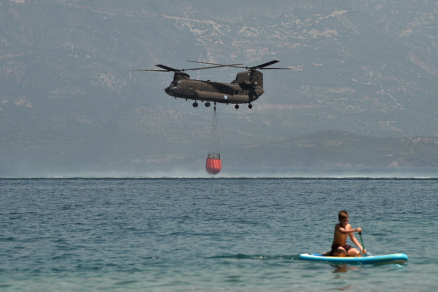 A helicopter retrieves water off the coast of Greece.