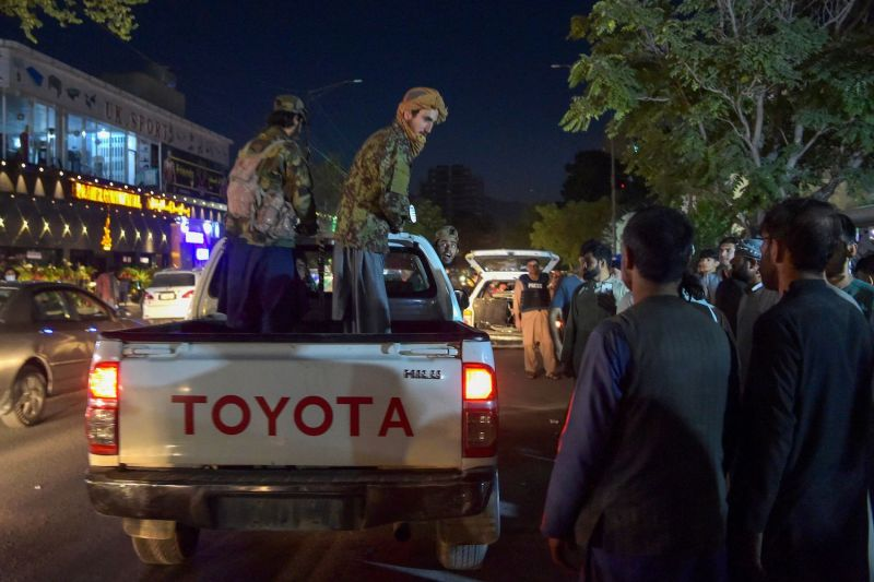 Taliban fighters stand on a pickup truck outside a hospital after explosions outside the Kabul airport.