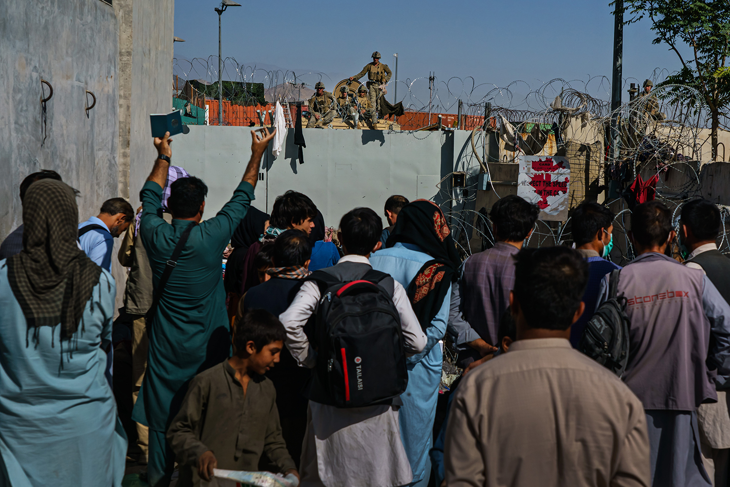 Afghans try to ask U.S. soldiers to let them into the Kabul airport.