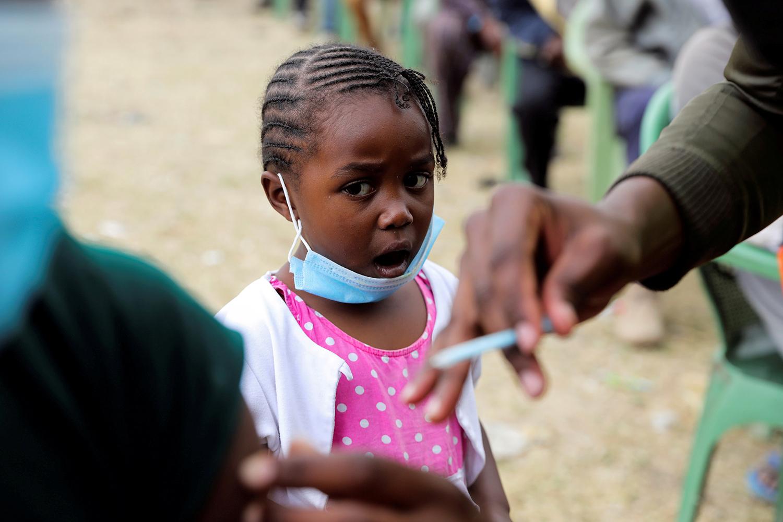 Girl watches dad get vaccine in Kenya