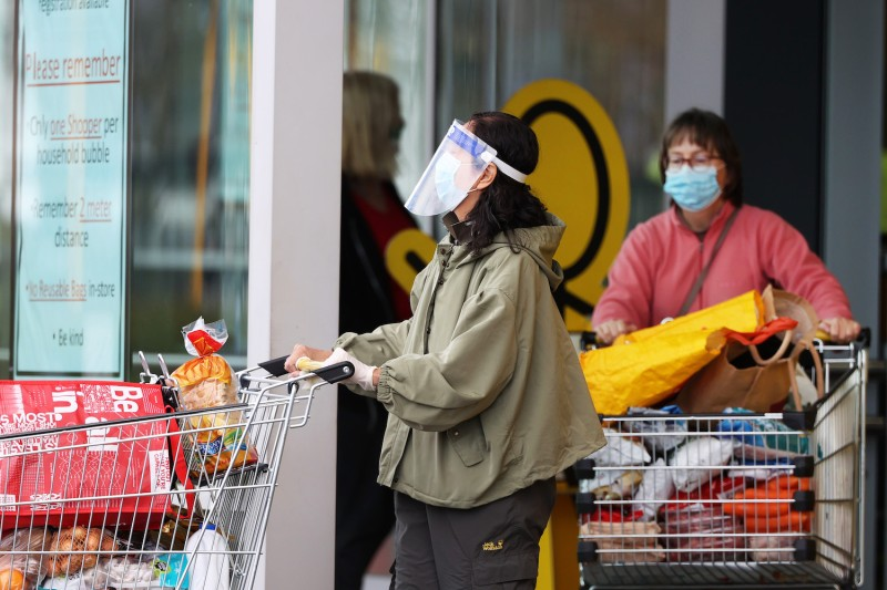 People wear masks at a supermarket in New Zealand.