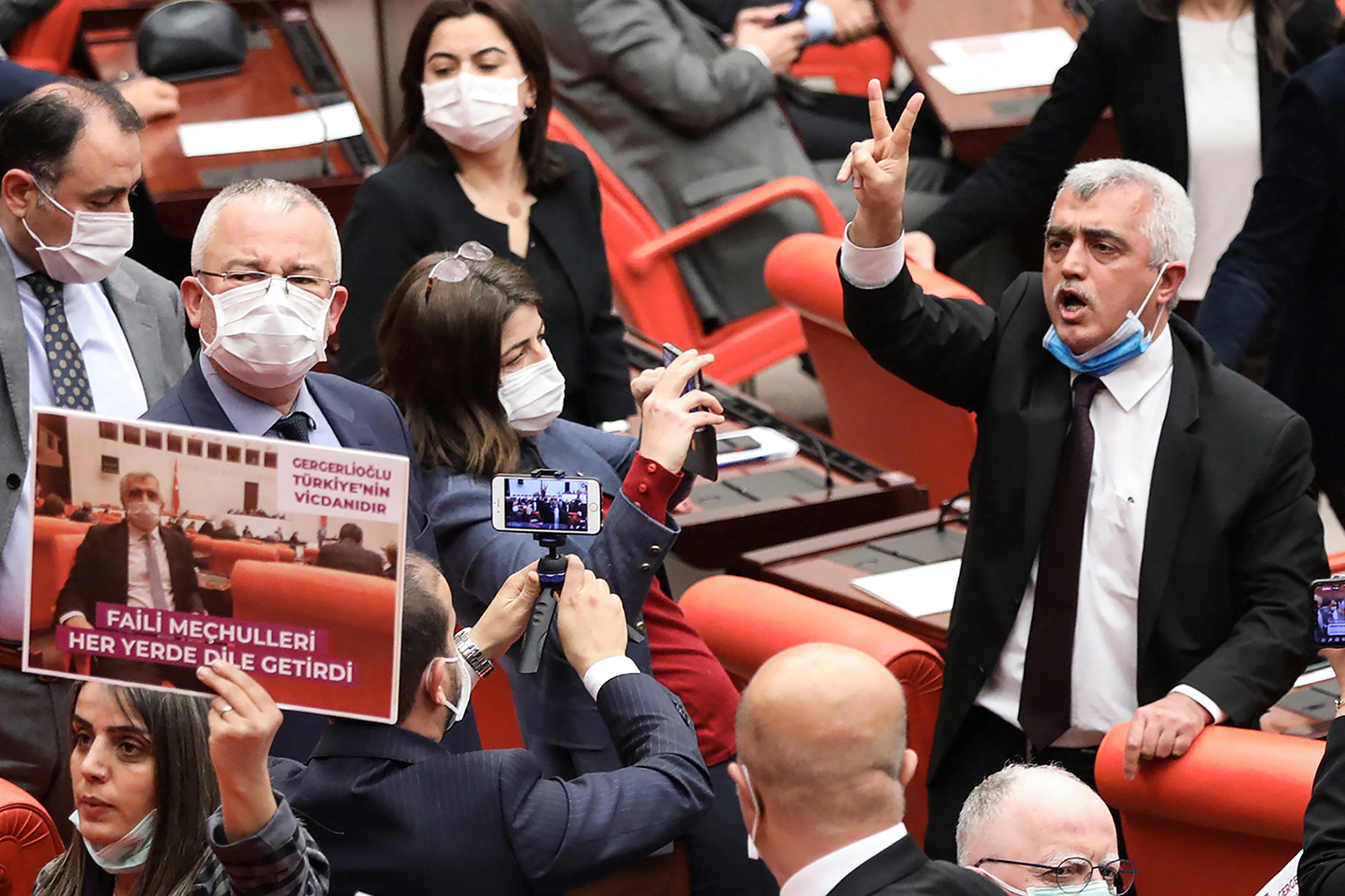 Omer Faruk Gergerlioglu, a Turkish member of parliament for the left-wing Peoples' Democratic Party, is surrounded by MPs applauding and brandishing placards after he was dismissed following a vote at the Turkish parliament in Ankara on March 17.