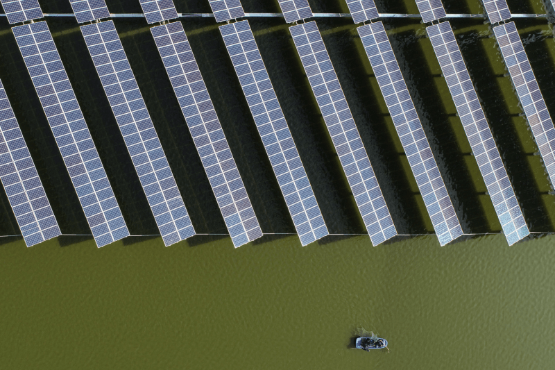 Chinese fishers next to a photovoltaic power station