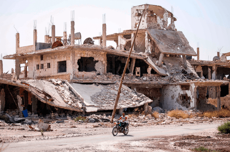 A man rides a motorcycle past destroyed buildings in an opposition-held neighborhood of the southern Syrian city of Daraa on Oct. 2, 2018.