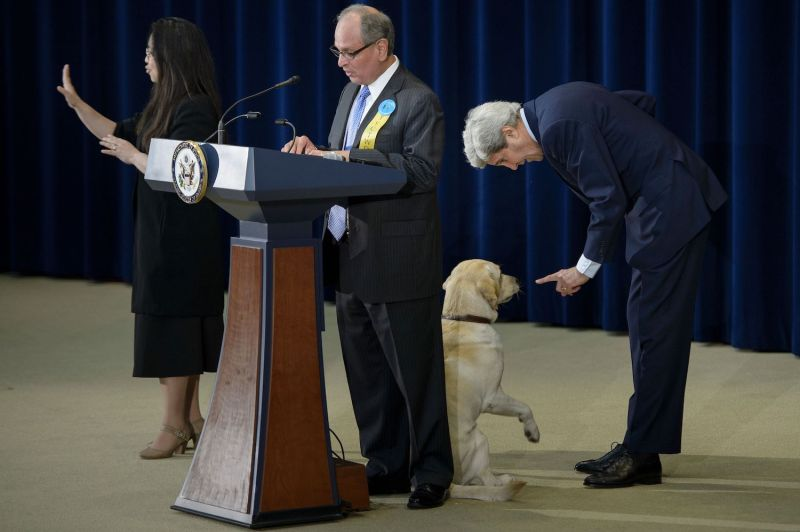 Then-U.S. Secretary of State John Kerry talks to his dog, Ben, at a State Department event.