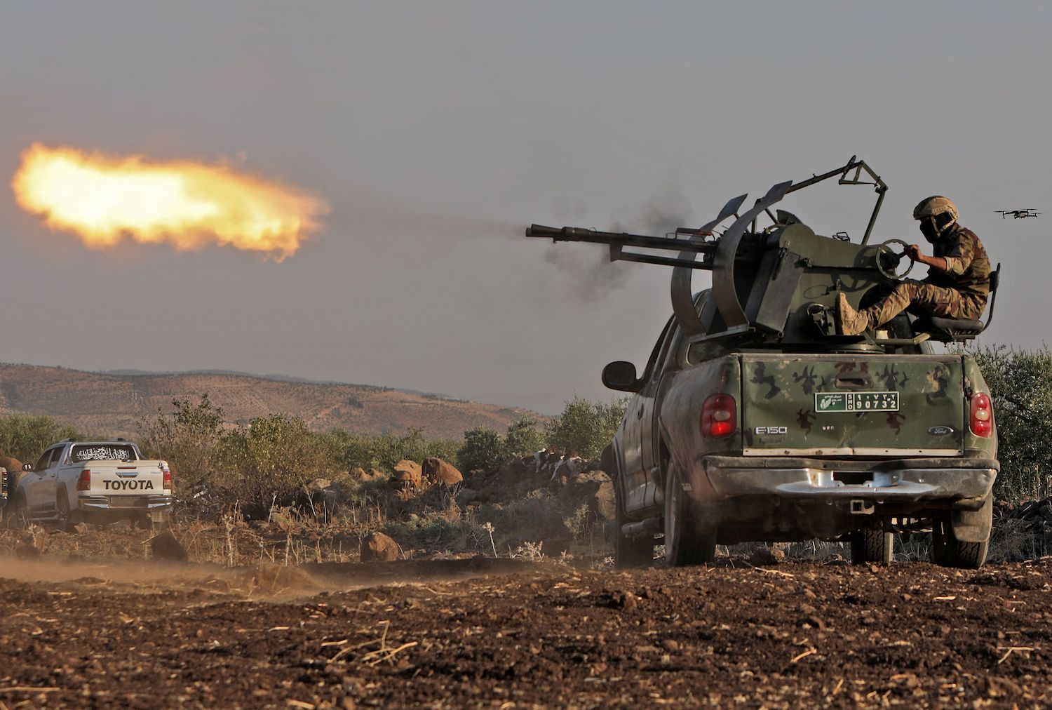 A Turkish-backed Syrian fighter opens fire from the back of a technical vehicle during military drills.