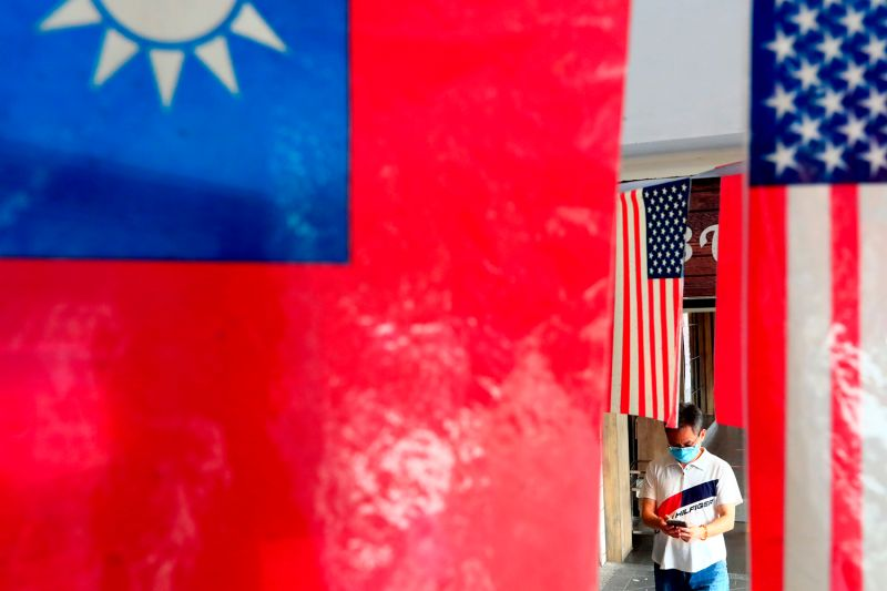 A man walks past U.S. and Taiwanese flags in Taipei on Aug. 10.
