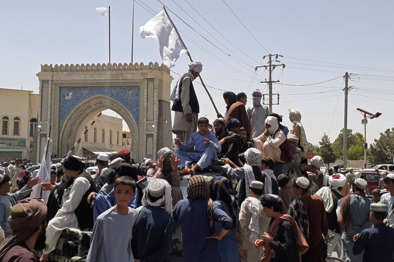 Taliban fighters stand on a vehicle.