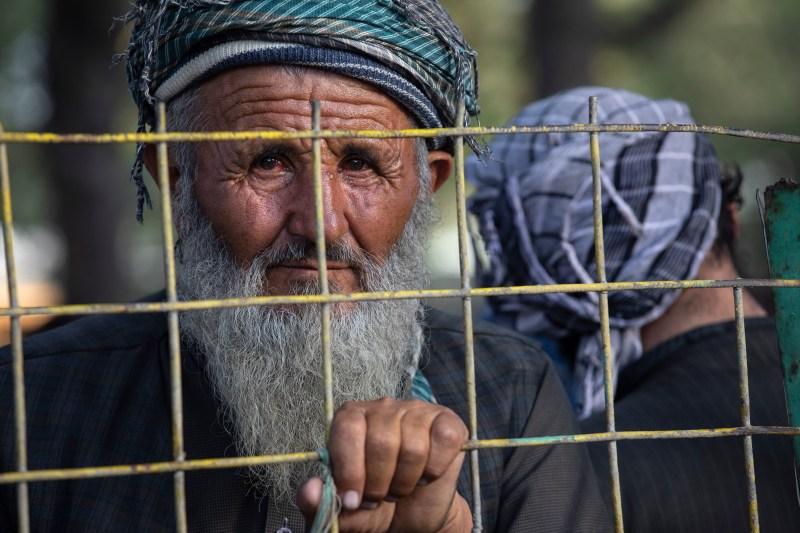 A man looks through an IDP fence in Kabul.