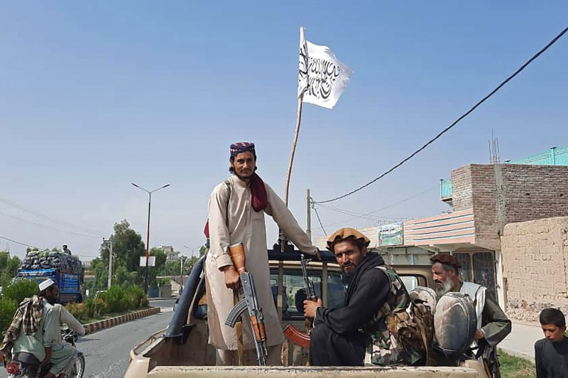 Taliban fighters drive an Afghan National Army vehicle