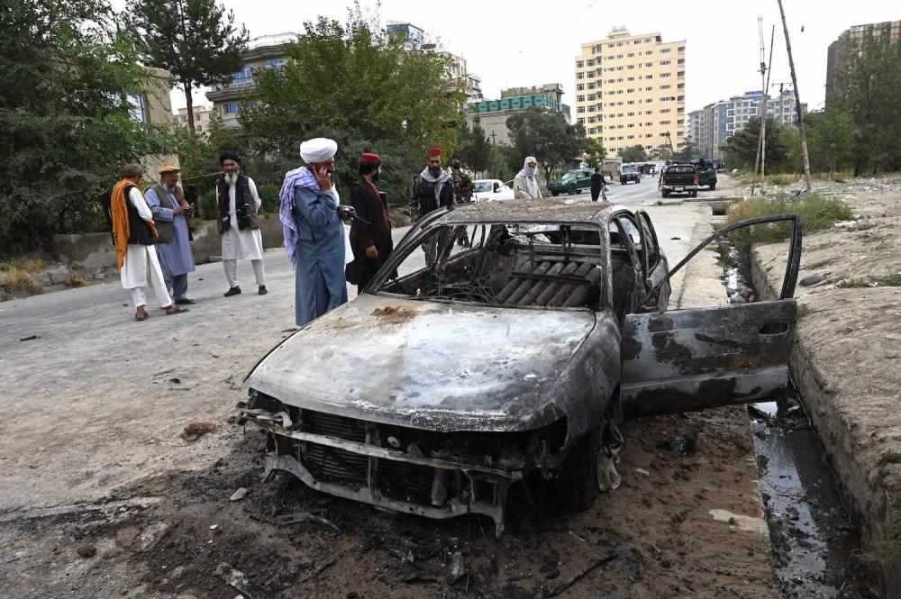 Taliban fighters investigate a damaged car.