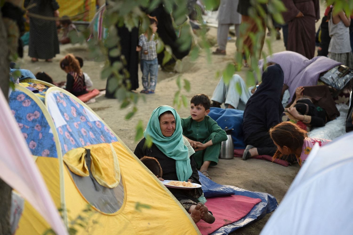 Internally displaced Afghan families who fled from Kunduz, Takhar, and Baghlan provinces sit near tents at Sara-e-Shamali in Kabul on Aug. 11.