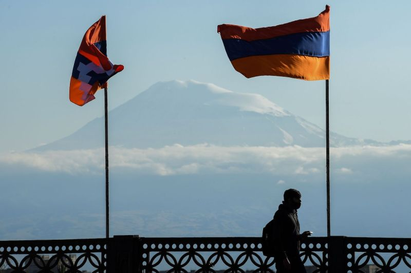 A man walks on a bridge decorated with flags of Armenia and the Nagorno-Karabakh region.