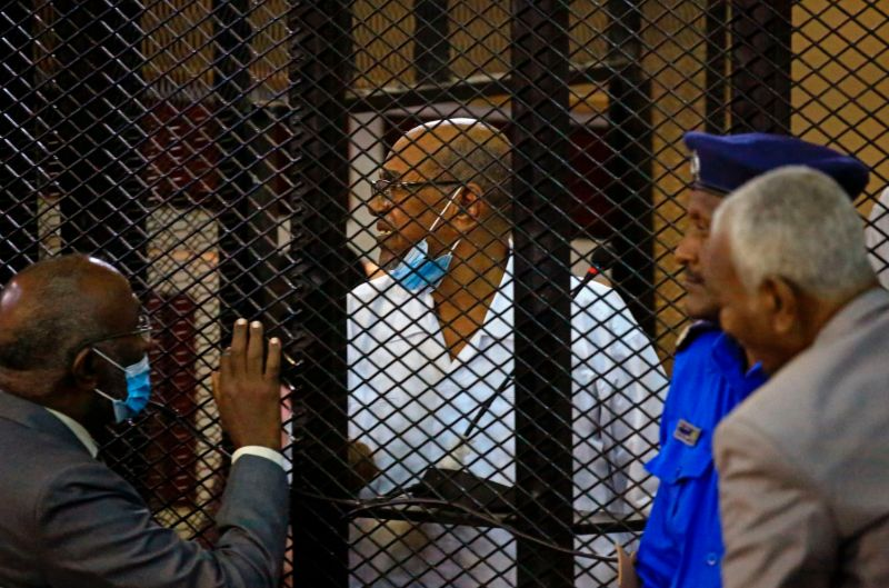 Sudan's ousted President Omar al-Bashir stands inside the defendant's cage during his trial over the 1989 military coup that brought him to power at a courthouse in Khartoum, Sudan, on Sept. 22, 2020.