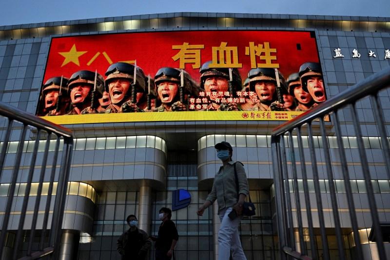 Pedestrians pass a military propaganda poster in Beijing.