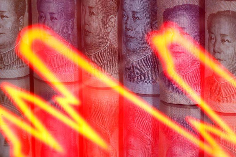 Chinese yuan banknotes are seen behind an illuminated stock graph on Feb. 10, 2020. Dado Ruvic Illustration/REUTERS