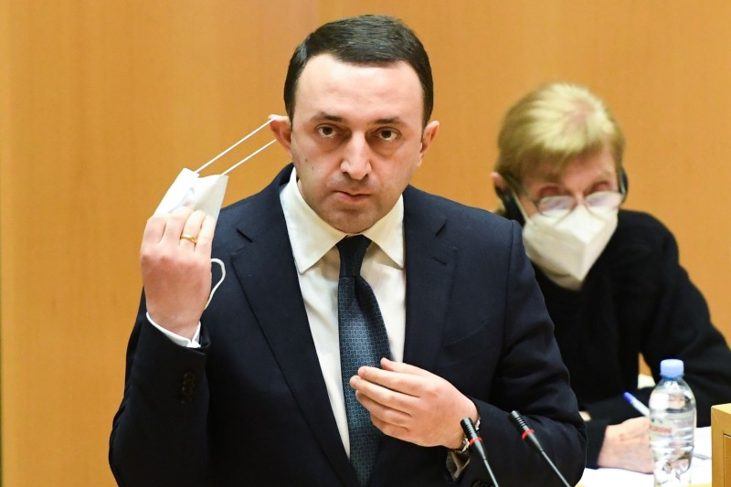 Georgian Prime Minister Irakli Garibashvili takes off his protective facemask before delivering a speech at the Georgian Parliament, in Tbilisi, on Feb. 22.