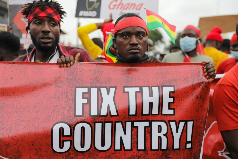 A Ghanian protester holds a banner.