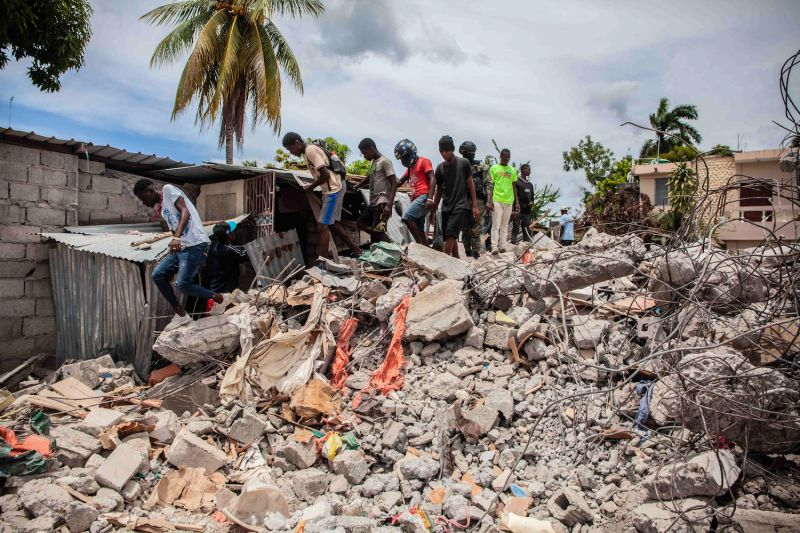 People walk over a pile of rubble from a collapsed building after a 7.2-magnitude earthquake in Les Cayes, Haiti, on Aug. 16.