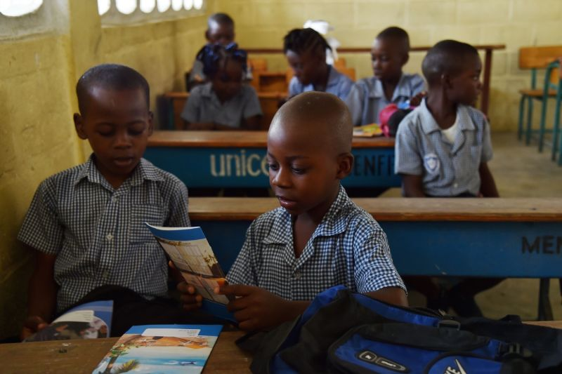 Students look at booklets at their desks on the first day back to school at the National School of Tabarre in the Haitian capital Port-au-Prince on Sept. 5, 2016.