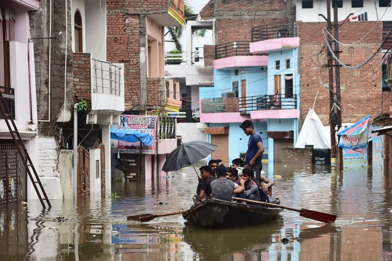 Residents ride a boat over a submerged road following heavy monsoon rains  in Allahabad, India, on Aug. 11.