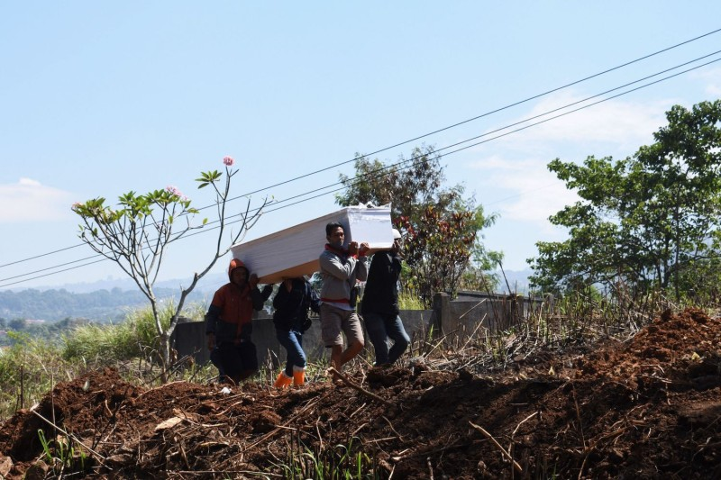 Gravediggers carry the coffin of a coronavirus victim in Indonesia.