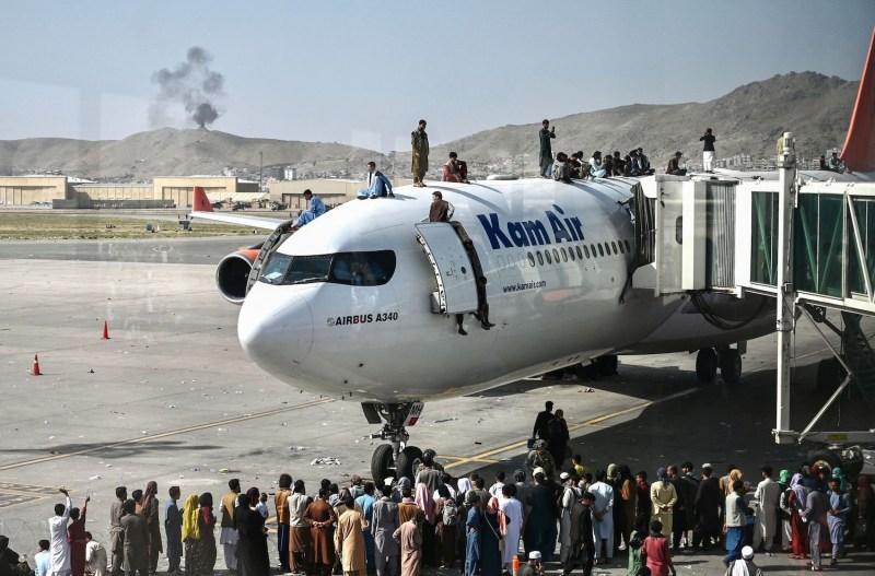 People climb atop a plane at Kabul airport