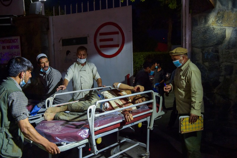 Medical and hospital staff bring an injured man on a stretcher for treatment after two powerful explosions outside the airport in Kabul on Aug. 26.