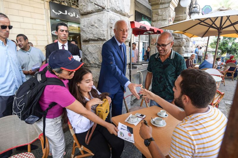 Kais Saied speaks with people during his presidential campaign tour in Tunis on September 10, 2019.