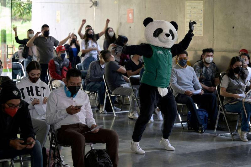 """A local government employee disguised as a panda called """"Pandemio"""" performs an exercise routine for people who have already received a first dose of the AstraZeneca vaccine against COVID-19 in Mexico City on Aug. 10."""