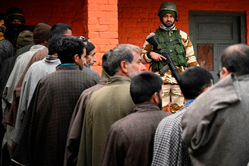 An Indian paramilitary soldier stands guard as voters wait to cast their ballots during the second phase of the District Development Council (DDC) and Panchayat by-elections at a polling station in Indian-administered Kashmir's Bandipora district on Dec. 1, 2020.