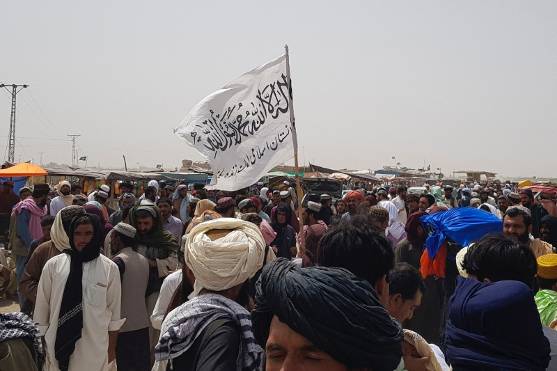 People gather around a Taliban flag near the Pakistan-Afghanistan border crossing point in Chaman, Pakistan, on Aug. 17.