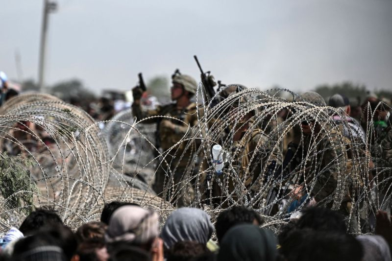 A U.S. soldier shoots in the air with his pistol while standing guard behind barbed wire as Afghans sit on a roadside near the military part of the airport in Kabul, Afghanistan on Aug. 20.