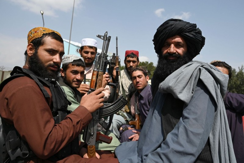 Taliban fighters sit on the back of a pickup truck at the airport in Kabul on Aug. 31.