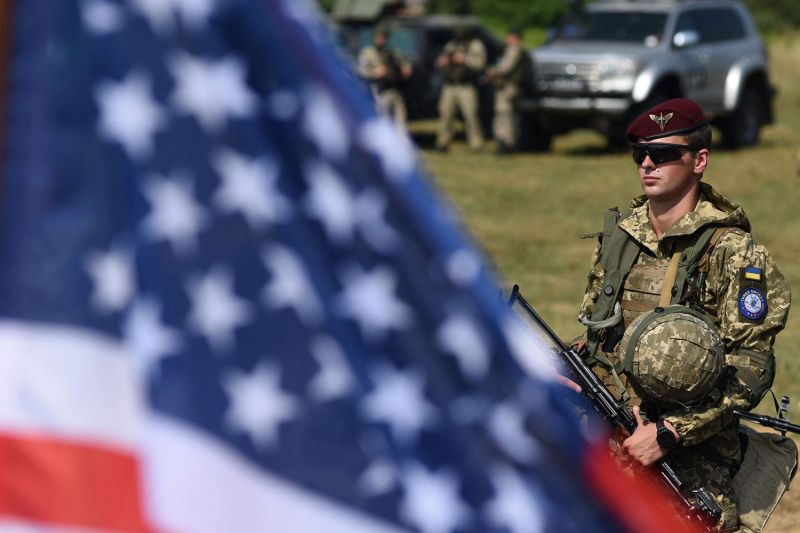 A Ukrainian serviceman walks past a flag of the United States.