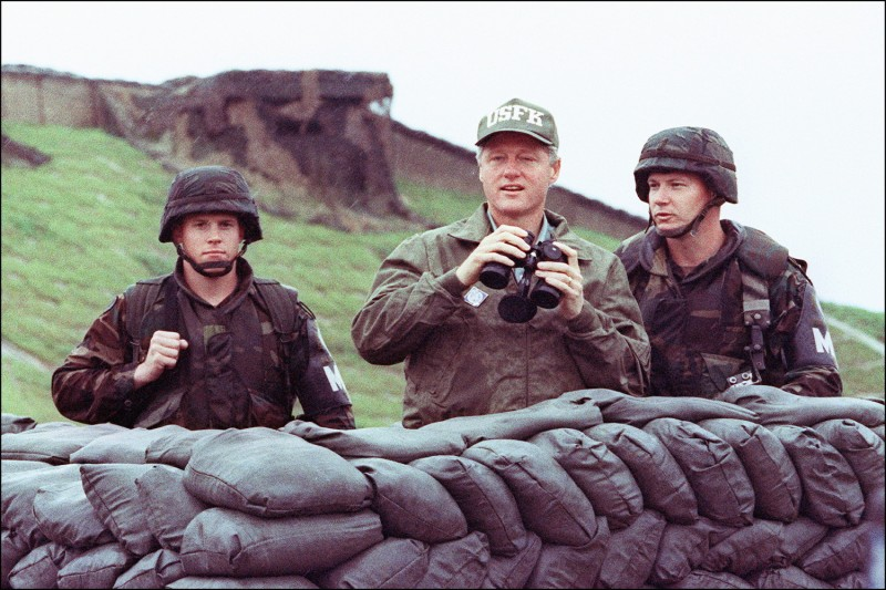 Then-U.S. President Bill Clinton uses binoculars to look across the Demilitarized Zone into North Korea with two U.S. soldiers during his trip to South Korea on July 11, 1993.