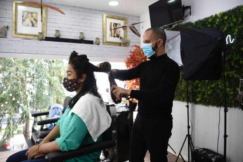 Venezuelan Angel Rodolfo Camaña combs a woman's hair at a hairdresser in Bogotá on Feb. 10.