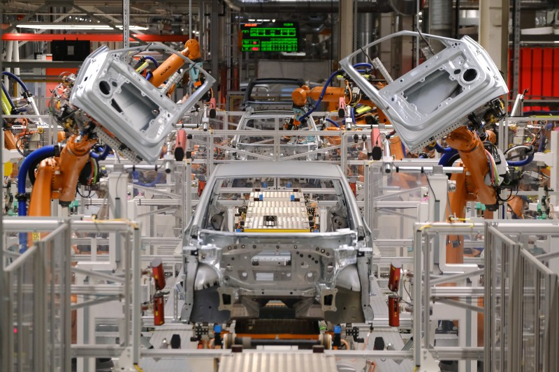 Industrial robots prepare to attach doors to the body of an ID.3 electric car at a Volkswagen factory in Zwickau, Germany, on Feb. 25, 2020.