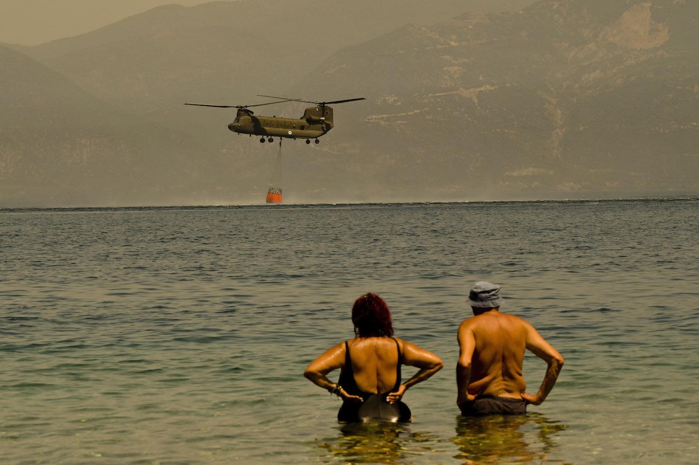 A Greek helicopter helps firefighters battle a wildfire in Greece.