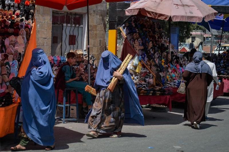 Burqa-clad women shop at a market in Kabul.