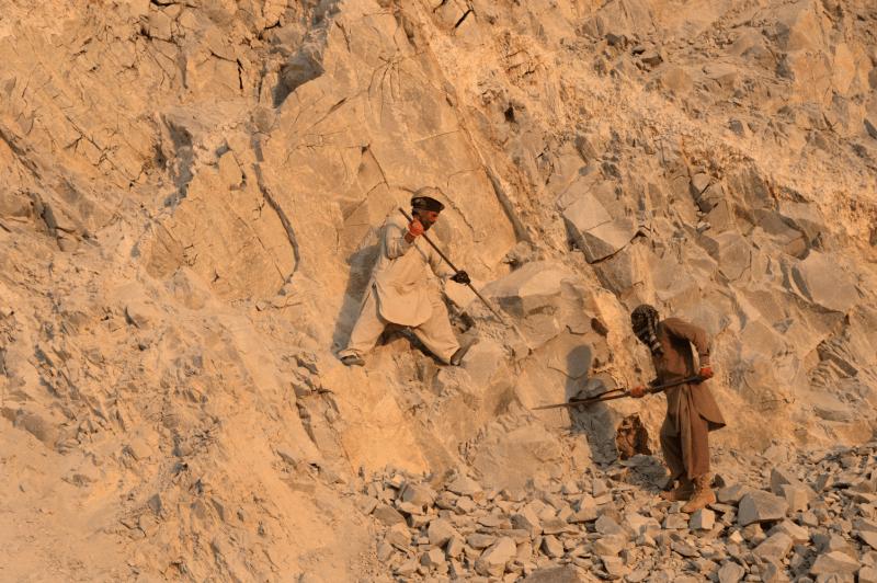 Afghan laborers work at a stone mine.