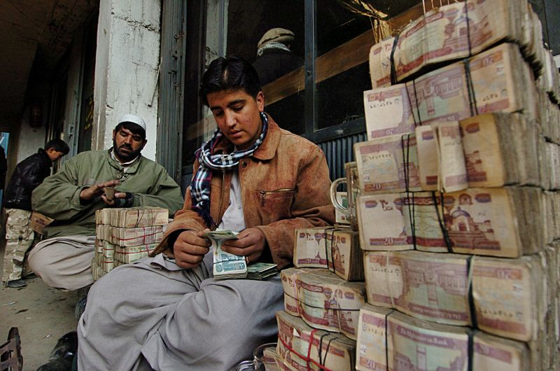 Afghan money-changers count Pakistani rupees at the money exchange market in Kabul.