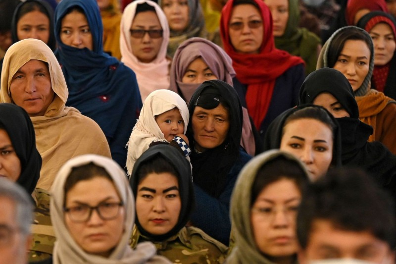 A Hazara woman holds her child as she attends an event on International Women's Day.